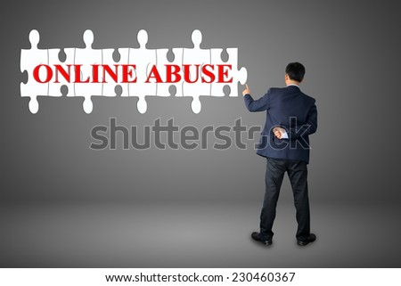 Businessman assembling complete a puzzle an insert word ONLINE ABUSE  - stock photo
