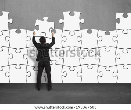 Businessman assembling puzzles wall - stock photo