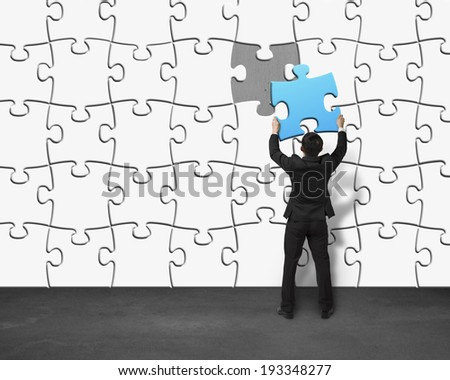 Businessman assembling unique blue puzzle into wall - stock photo