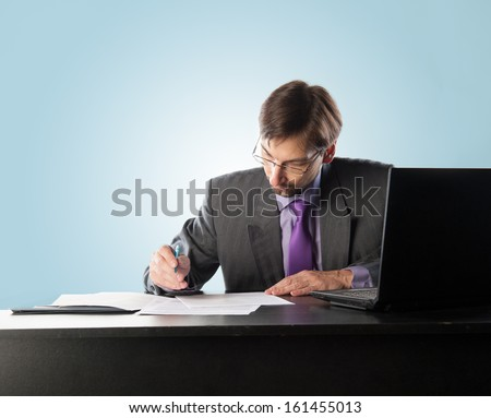 businessman at his desk with a laptop and papers - stock photo