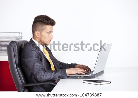 Businessman at his office working with his laptop - stock photo