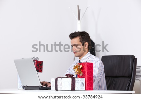 Businessman at his office working with his laptop with presents on the table - stock photo