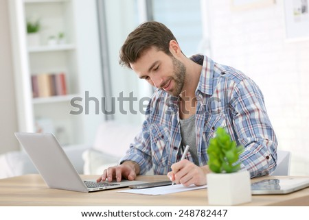 Businessman at home working on laptop - stock photo