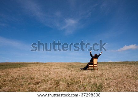 businessman at the field relaxing and enjoying nature - stock photo