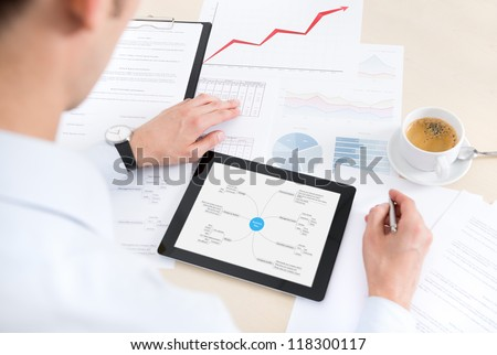 Businessman at the workplace working with documents and using modern digital tablet. Some papers with charts and graphs and cup of coffee on a desktop. - stock photo