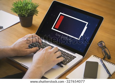Businessman at work. Close-up top view of man working on laptop with low battery. all screen graphics are made up. - stock photo