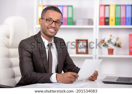 Businessman at work. Confident young African businessman working in his office - stock photo