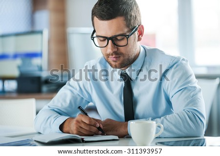 Businessman at work. Confident young businessman in formalwear writing in note pad while sitting at his working place  - stock photo