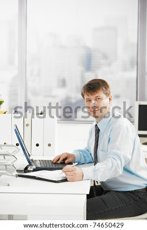 Businessman at work, searching in personal organizer, using laptop. Looking at camera.? - stock photo