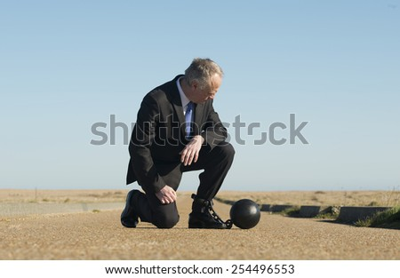 Businessman attached to a ball & chain. - stock photo