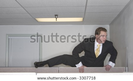 Businessman attempts to climb up over his cubicle in an attempt to get out of his office while looking at the camera - stock photo