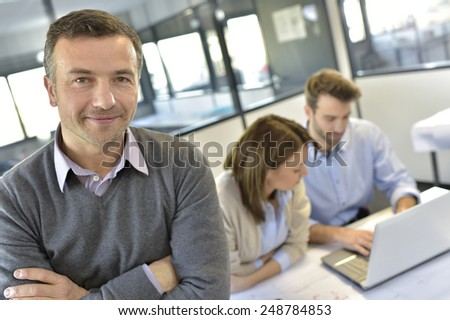Businessman attending meeting with workteam - stock photo