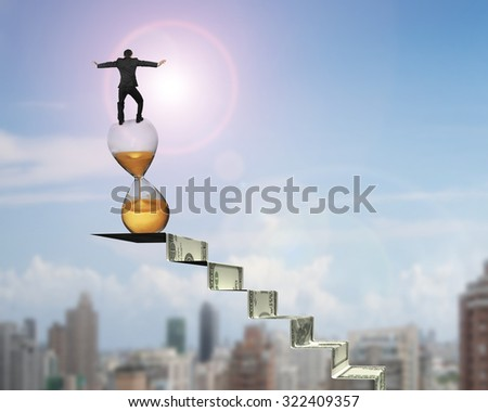 Businessman balancing hourglass on top of money stairs, with sun sky cityscape background. - stock photo