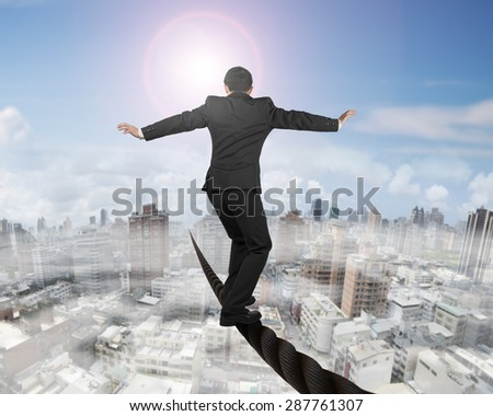 Businessman balancing on a wire with sky sun mist cityscape background. - stock photo