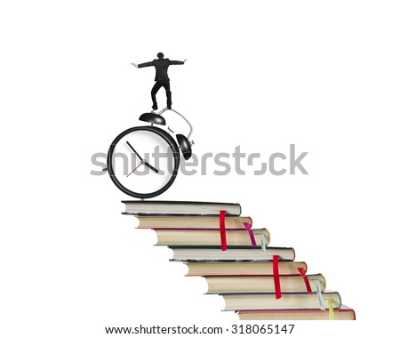 Businessman balancing on alarm clock and stack of books, isolated on white background. - stock photo