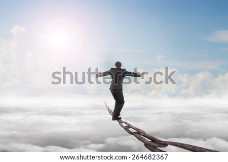 Businessman balancing on old iron chain with sky sunlight cloudscape background - stock photo