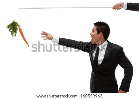 Businessman being tempted and reaching for a carrot at the end of a stick - stock photo