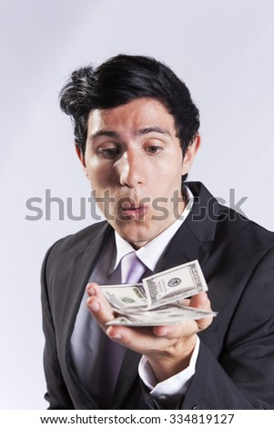 businessman blowing at money from his hands (isolated on gray) - stock photo