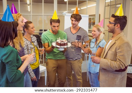 Businessman blowing candles on her birthday cake in the office - stock photo