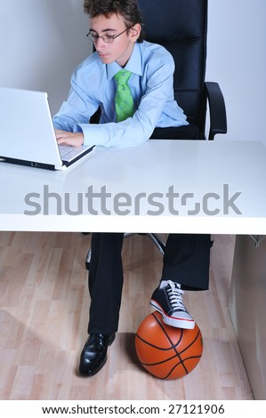 Businessman booted with a business shoe in a foot and a sneaker on the other using laptop and keeping basketball under the desk - stock photo