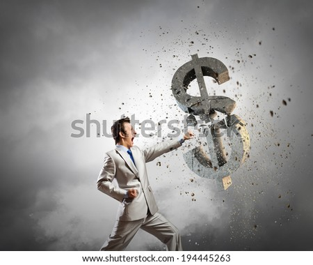 Businessman breaking stone dollar symbol with karate punch - stock photo