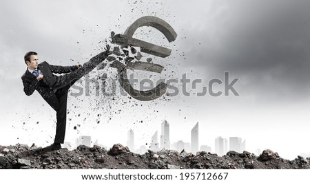 Businessman breaking stone euro symbol with karate punch - stock photo
