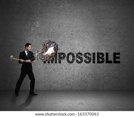 businessman breaks the wall with impossible - stock photo