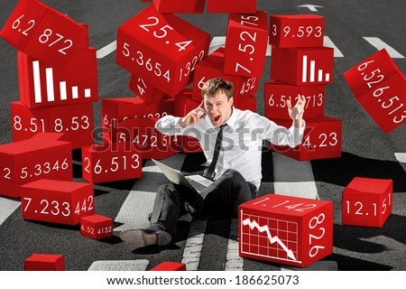 businessman broker shocked about collapse of shares on the stock exchange sitting with laptop on the asphalt surrounded by red boxes - stock photo