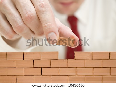 businessman building a wall - stock photo