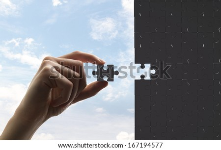 businessman built of puzzle on sky background - stock photo
