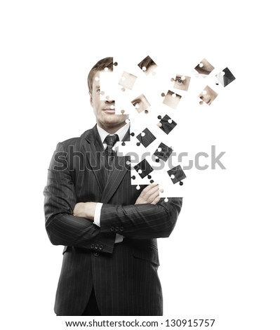 businessman built of puzzle on white background - stock photo