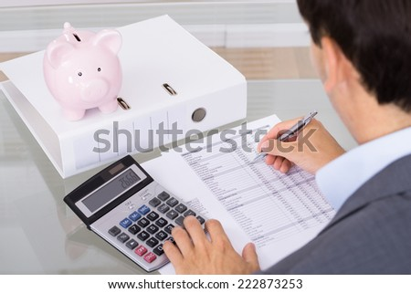 Businessman calculating finances. Over the shoulder view - stock photo
