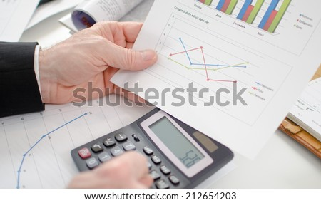 Businessman calculating financial results at his desk - stock photo