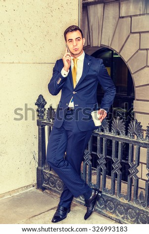 Businessman calling on cell phone while taking break during work, dressing in striped blue suit, yellow tie, leather shoes, holding coffee cup, standing on balcony outside office. Instagram effect.  - stock photo