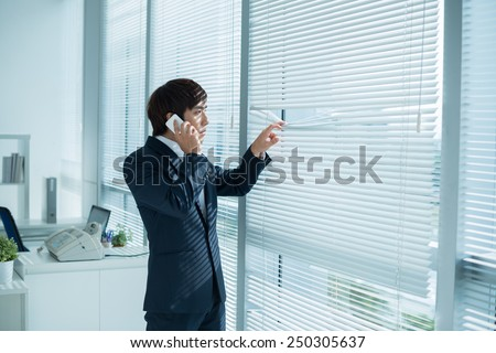 Businessman calling on the phone and looking out of the window through the blinds - stock photo