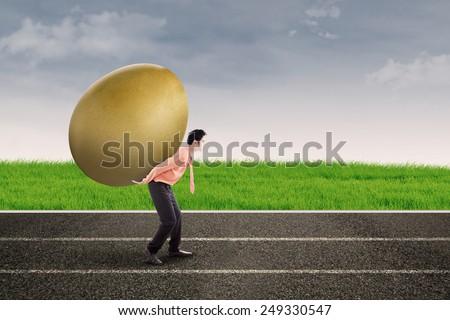 Businessman carry big golden egg outdoor - stock photo
