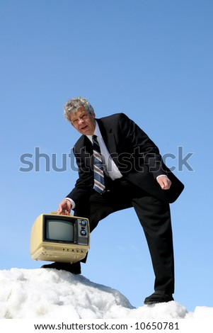 Businessman carrying an old TV - stock photo
