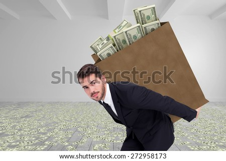 Businessman carrying bag of dollars against big room with white wall - stock photo