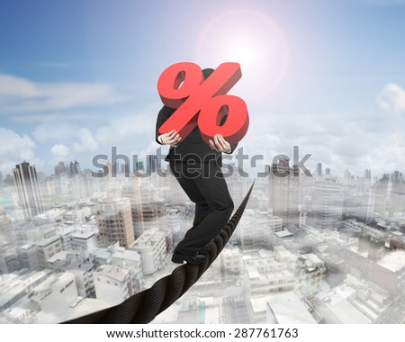 Businessman carrying 3D red percentage sign balancing on a wire, with sky sun mist cityscape background. - stock photo