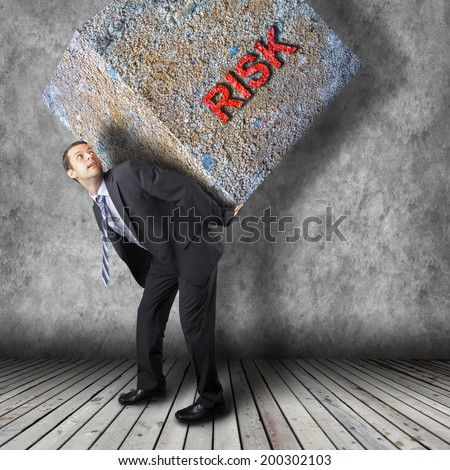Businessman carrying heavy package - concept of tough career in the business - stock photo