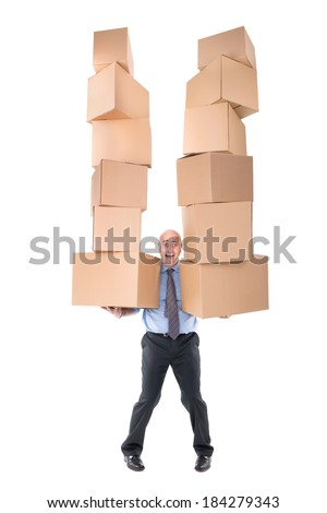 Businessman carrying piles of cardboard boxes - stock photo