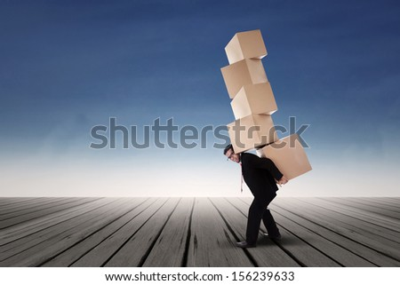 Businessman carrying with stack of boxes - stock photo