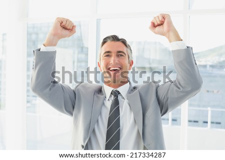 Businessman celebrating a good job in his office - stock photo