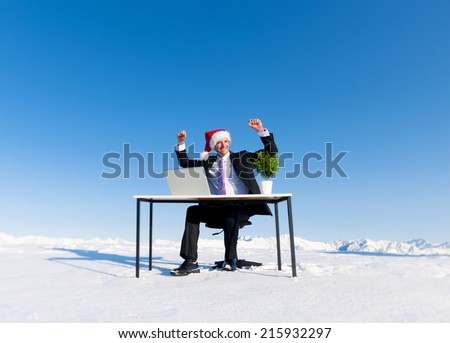 Businessman celebrating christmas on snow covered mountain. - stock photo