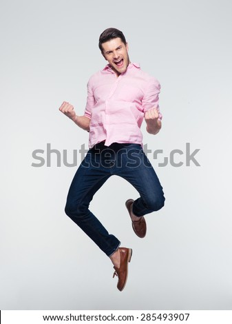 Businessman celebrating his success and jumping over gray background. Looking at camera - stock photo