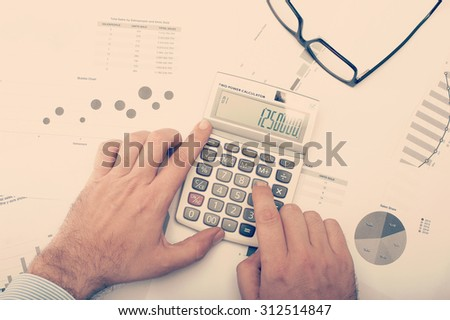 Businessman checking charts and statistics and using calculator on desktop - stock photo