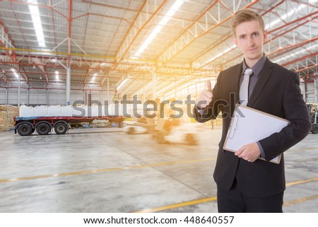 Businessman  checking complete product for import and export with forklift loading goods in warehouse background for import export business. - stock photo
