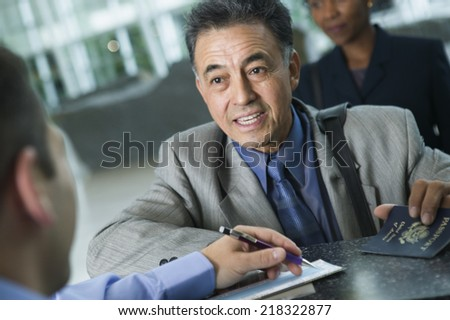 Businessman checking in at airport - stock photo