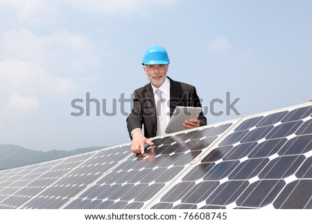 Businessman checking photovoltaic installation - stock photo