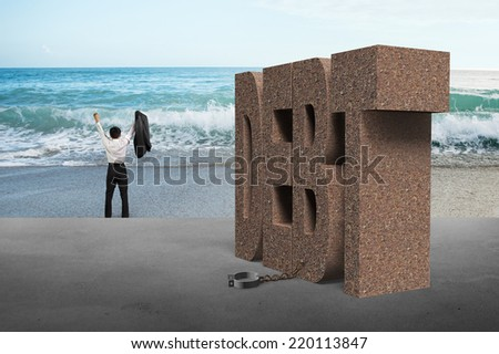 businessman cheering for free from DEBT shackle with sea - stock photo